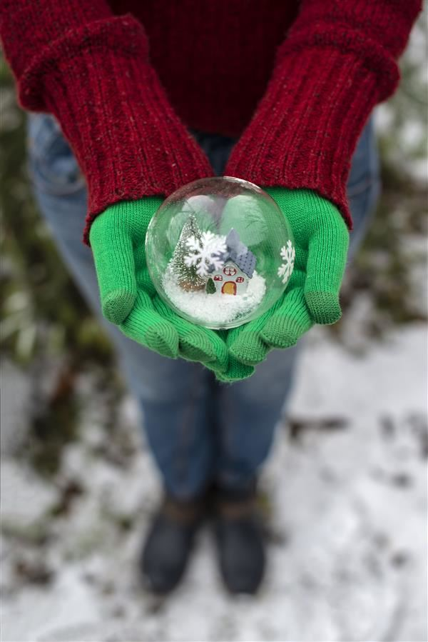 Hands holding Christmas ball with house and snow inside