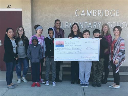 Cambridge Staff and Students Holding Donation Check