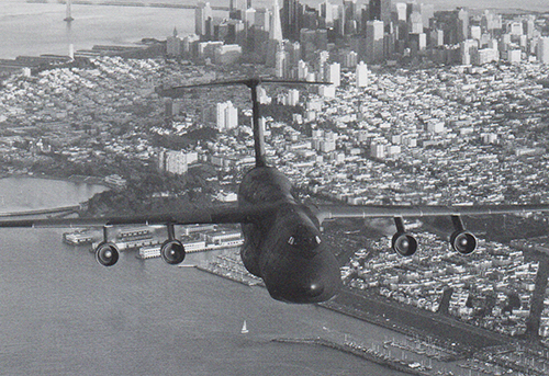 Historical photo of C-5 Galaxy in flight with city beneath