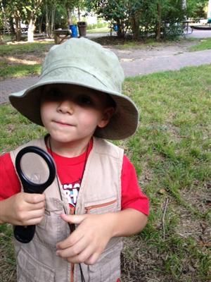 A photo of a young child in a hat holding a magnifier glass